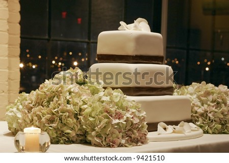 beautiful wedding cake and hydrangeas displayed on table