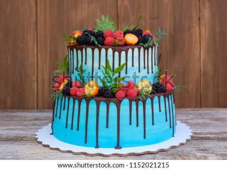 beautiful wedding cake in two tiers, decorated with fresh raspberries, blackberries, blueberries, chocolate icing #1152021215