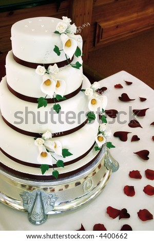 stock photo Beautiful wedding cake with flower details and petals on table