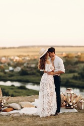 Beautiful wedding couple in nature in boho style. Wedding in the European style of fineart at sunset.