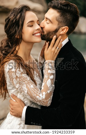 Beautiful wedding couple laugh and kiss on the background of stones. High quality photo Сток-фото ©