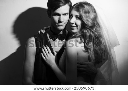 Beautiful wedding couple standing beside on white wall background. Hug each other. Black and white portrait  #250590673