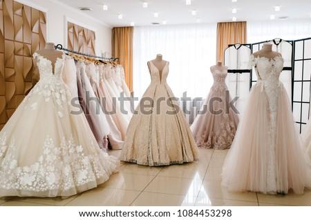 Beautiful wedding dresses, bridal dress hanging on hangers and mannequin in studio. Fashion look. Interior of bridal salon. Сток-фото ©