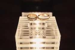 Beautiful wedding rings lie on a wooden surface