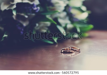 Beautiful wedding rings lie on a wooden surface against the background of a bouquet of flowers
