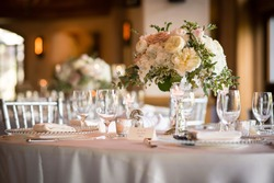 Beautiful wedding table setting for celebration of marriage and love with flowers and floral arrangement plus silverware, dinnerware, glassware, and luxurious romantic decor.