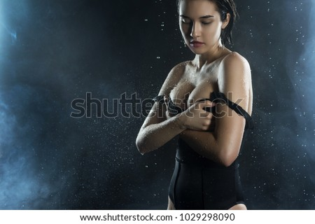 Beautiful wet big breasted girl wearing black swimsuit on a dark background. Falling rain drops and artistic scenic smoke. Advertising, commercial design. Copy space. Mixed Asian-Caucasian race.