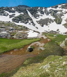 Beautiful wetland from spring, melting ice and snow, alpine mountain meadow called Paradies with lush green grass and blue sky. Stubai hiking trail, Summer Tirol Alps, Austria
