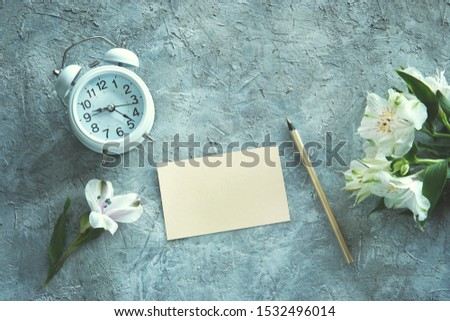 Beautiful white alstroemeria flowers  with white alarm clock and a free space for message on pastel paper with a pencil. Top view, copy space. Textured grey background. Morning light.             #1532496014