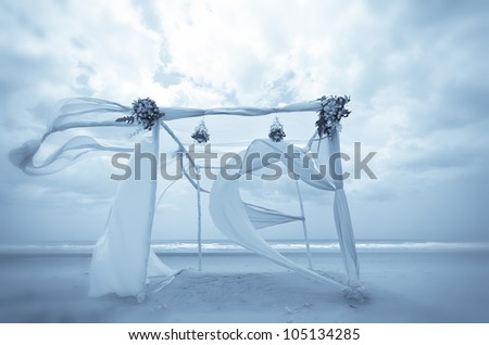 Beautiful white and blue tent on a beach in windy day in vintage style