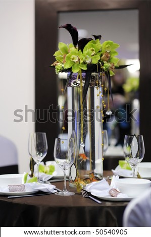 Beautiful white and chocolate festive table with gold fish - stock photo