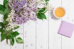 Beautiful white and violet lilac flowers with closed note-book and cup of tea on the white wooden background, mock up top flat view