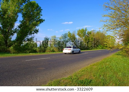 Beautiful white car on road across forest. Shot in Ukraine.