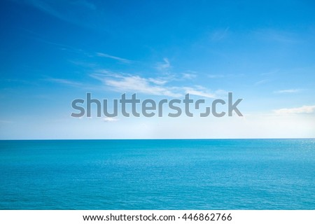 Beautiful white clouds on blue sky over calm sea with sunlight reflection, Bali Indonesia. Tranquil sea harmony of calm water surface. Sunny sky and calm blue ocean. Vibrant sea with clouds on horizon #446862766