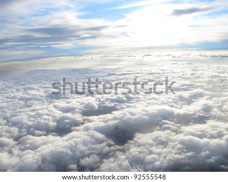 Beautiful white clouds under sunshine, shot on a airplane, above the clouds, blue sky