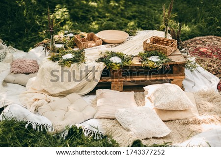 Beautiful white decor in boho style. Picnic in nature, table, carpets, wigwam, tent, pillows in the park. Celebration after quarantine.