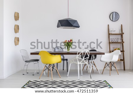 Beautiful white dining room with a large table and designer chairs