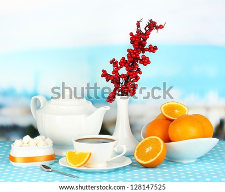 Beautiful white dinner service with oranges on blue tablecloth on natural background