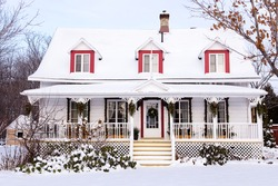 Beautiful white french-style ancestral house with pitched roof and decorative wooden trim seen with a fresh coat of snow during a sunny winter day, Saint-Nicolas, Quebec, Canada