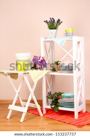 Beautiful white furniture with tableware and decor, on color wall background