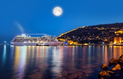 Beautiful white giant luxury cruise ship on stay at Alanya harbor with full moon