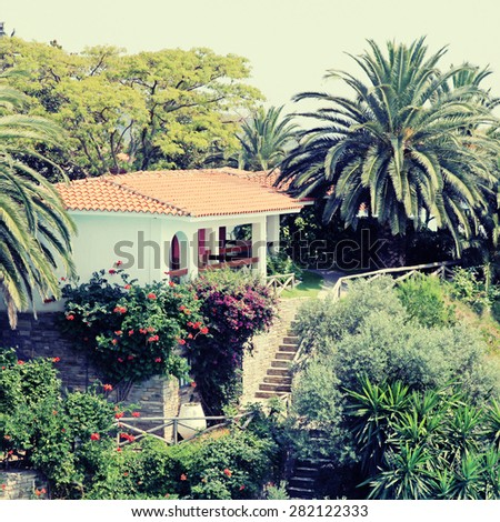Beautiful white house with red tile roof, small terrace and steps in the mediterranean garden, Greece. Square toned image, instagram effect