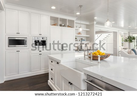 Beautiful White Kitchen Detail in New Luxury Home: shows floor to ceiling cabinets, farmhouse sink, faucet, refrigerator, microwave, and coffeemaker