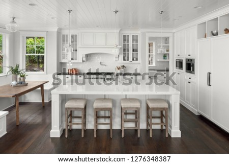 Beautiful White Kitchen in New Luxury Home. Features Hardwood Floors, Eating Nook, Island with Sink, and Built-In Refrigerator. #1276348387