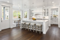 Beautiful White Kitchen in New Luxury Home. Features large island, eating nook, hardwood floors, and second sink.