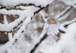 beautiful white little doll - an angel hangs on  snow-covered tree branches. Day Angel. Festive mood, time for gifts and miracles. Winter, cold. Christmas Eve