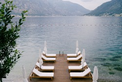 Beautiful white loungers and beach umbrellas on the pier in Kotor Bay, Montenegro.
