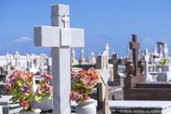 Beautiful white marble cross and flowers among many other crosses and grave markers at cemetery in Old San Juan, Puerto Rico