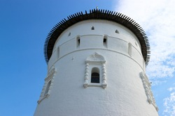 beautiful white old tower of the fortress Rostov kremlin against the bright summer sky