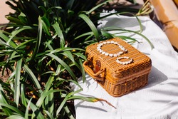 Beautiful white shell jewerly bracelet and necklace on brown wicker chest and white beach carpet by tropical leafs, outdoor shot.