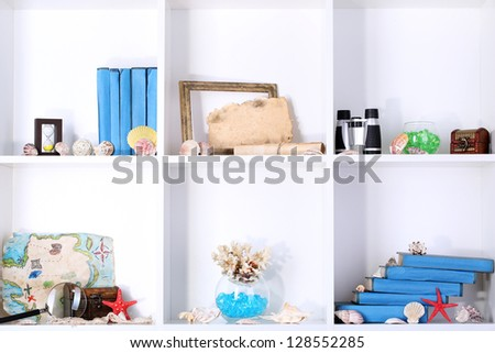 Beautiful white shelves with different travel related objects - stock photo