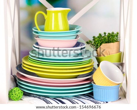 Beautiful white shelves with tableware and decor, on bright background, close-up