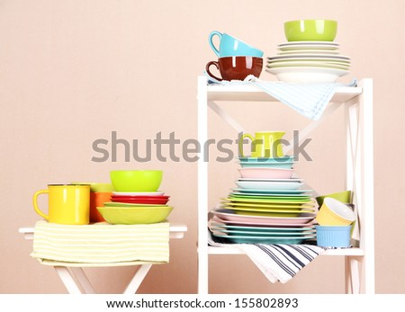 Beautiful white shelves with tableware and decor, on color wall background, close-up