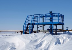 Beautiful white snow on the background of a gas well