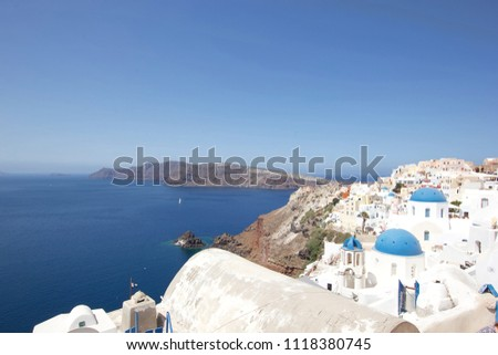 Beautiful white washed buildings against the Aegean sea with mountains and boats in the distance, Santorini, Greece