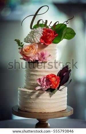 Beautiful white wedding cake with roses as decoration