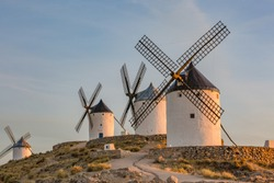 Beautiful white windmill on the hill with blue cloudy sunset sky background