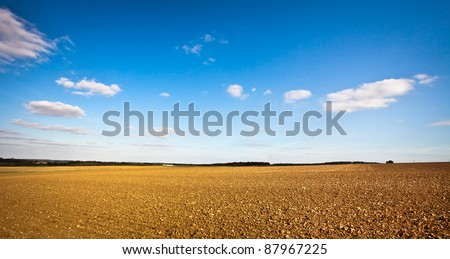 Beautiful wide angle image of a freshly tilled field in the UK on a crisp autumn day, could be used as a template with plenty of copyspace - stock photo