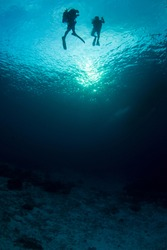 Beautiful wide angle shot of two divers descending in clear blue deep water over a sandy bottom. Early morning sun is behind and the ocean is 40 meters deep. Amazing backdrop.