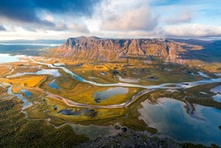 Beautiful, wild arctic valley viewed from mountain top in epic early morning light. Remote Rapa river valley from the top of Skierfe in Sarek national park in Swedish Lapland. Autumn colors.