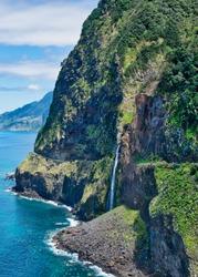 Beautiful wild coast view with Bridal Veil Falls (Veu da noiva) near Porto Moniz and Seixal in Madeira Island, Portugal