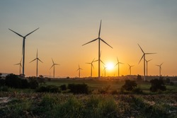 Beautiful wind turbine on the field in sunset time background