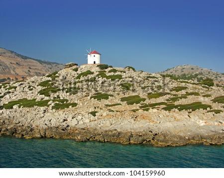 beautiful windmill on small island near rhodes, greece
