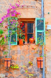 Beautiful window with flower pots and colorful flowers serving as a decoration of the facade. The flowers have bright pink, red and yellow Colors. Taken in spanish village Valldemossa, Mallorca.