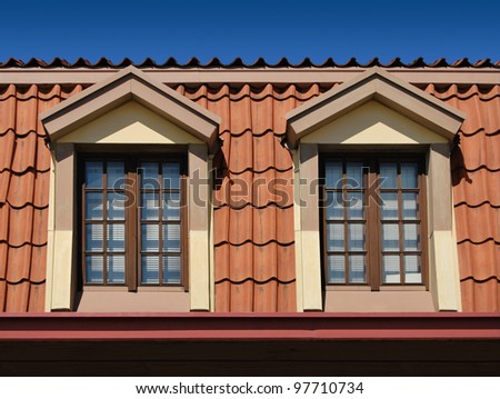 Beautiful windows in the loft attic coated with terracotta