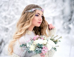 Beautiful winter bride with loose hair with a bouquet during a snowfall in the forest. The concept of beauty and winter wedding.
